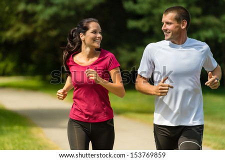 Portrait of cheerful Caucasian couple running outdoors - stock photo