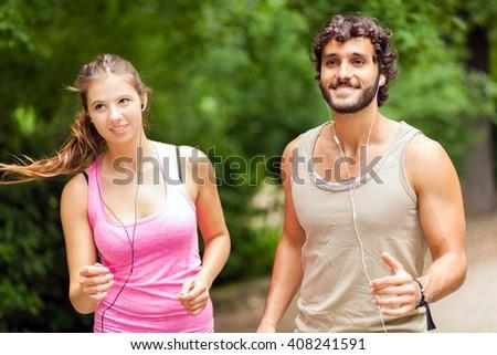 Portrait of cheerful Caucasian couple running outdoors - stock photo