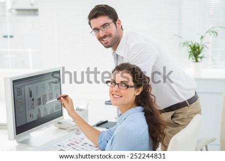 Portrait of cheerful colleagues using computer in the office