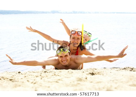 Portrait of cheerful couple and their son in diving equipment lying on sand and looking at camera - stock photo