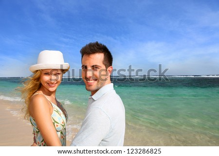 Portrait of cheerful couple at the beach - stock photo