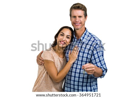 Portrait of cheerful couple holding home keys against white background