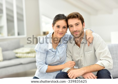 Portrait of cheerful couple sitting in sofa at home - stock photo