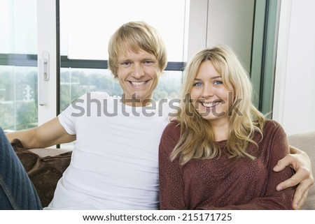 Portrait of cheerful couple sitting on sofa at home - stock photo