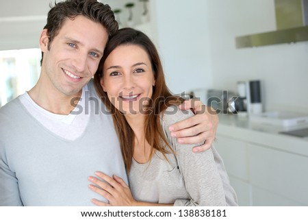Portrait of cheerful couple standing at home - stock photo