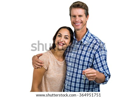Portrait of cheerful couple with keys standing against white background - stock photo