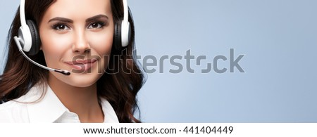 Portrait of cheerful customer support female phone operator in headset, against grey background. Consulting and assistance service call center. - stock photo