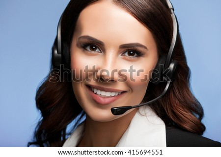 Portrait of cheerful customer support female phone operator in headset, over blue background. Consulting and assistance service call center. - stock photo
