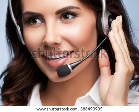 Portrait of cheerful customer support female phone operator in headset, over grey background. Consulting and assistance service call center. - stock photo