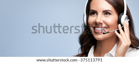 Portrait of cheerful customer support female phone worker, looking up, with copyspace, on grey background. Consulting and assistance service call center. - stock photo