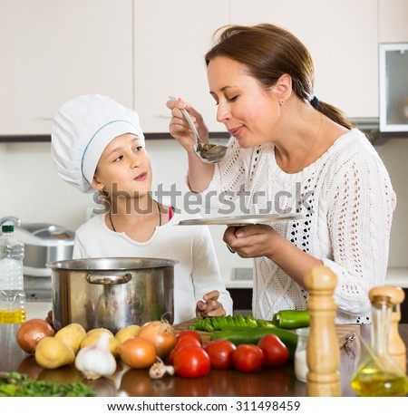 Portrait of cheerful daughter and mom with vegetables and casserole in kitchen at home. Focus on girl - stock photo