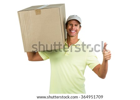 Portrait of cheerful delivery man with box showing thumbs up against white background - stock photo