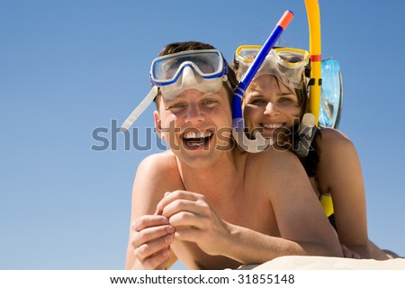 Portrait of cheerful divers lying on sand and enjoying themselves