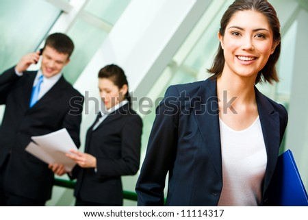 Portrait of cheerful employee in suit holding the folder on the background of business people