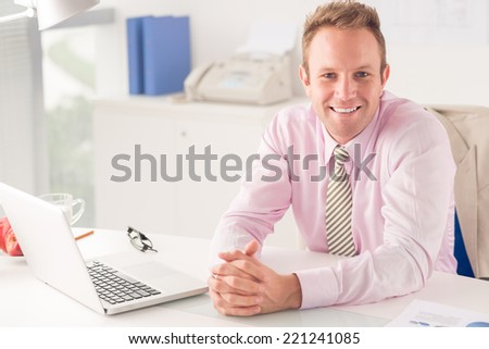 Portrait of cheerful entrepreneur at his workplace - stock photo