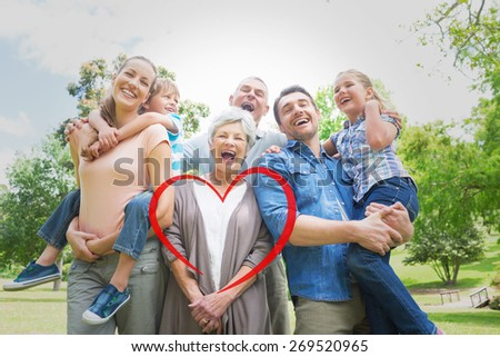 Portrait of cheerful extended family at park against heart - stock photo