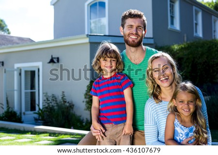 Portrait of cheerful family against house - stock photo