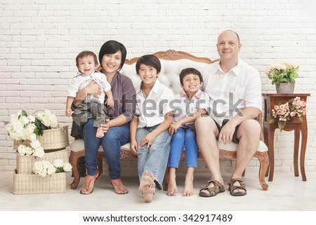 portrait of cheerful family at home sitting on sofa
