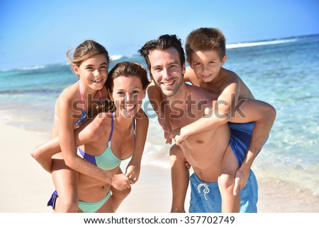 Portrait of cheerful family at the beach, piggyback ride - stock photo