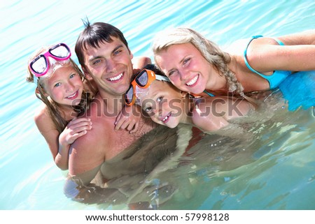 Portrait of cheerful family looking at camera from water