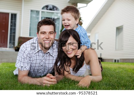 Portrait of cheerful family lying down on grass in front of house - stock photo