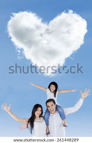 Portrait of cheerful family raise hands together and enjoy freedom under cloud shaped heart - stock photo