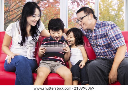 Portrait of cheerful family sharing digital tablet for play game on sofa with autumn background - stock photo