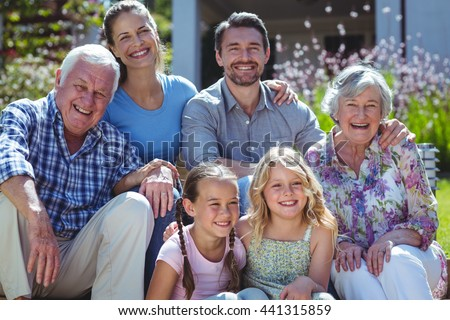 Portrait of cheerful family sitting in back yard - stock photo