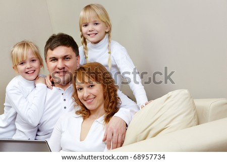 Portrait of cheerful family sitting on the sofa in the room - stock photo
