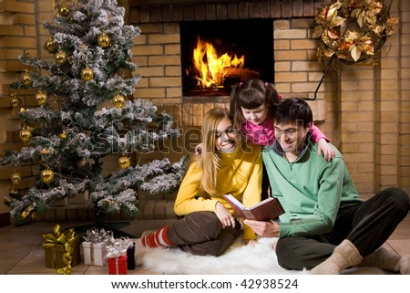 Portrait of cheerful family sitting on white fur reading old book with decorated fir tree near by