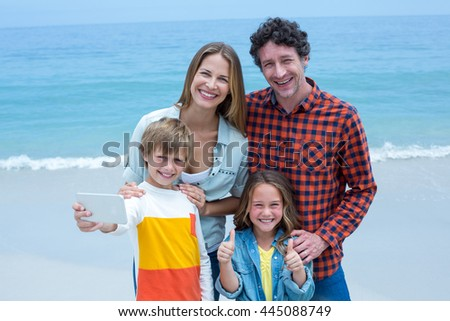 Portrait of cheerful family taking selfie while standing at sea shore - stock photo