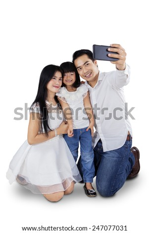 Portrait of cheerful family using mobile phone to take self photo in the studio - stock photo