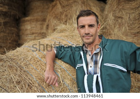 Portrait of cheerful farmer standing in front of hay rolls