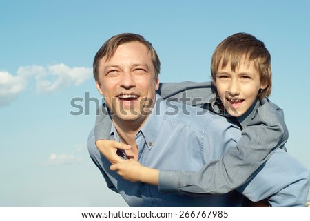 portrait of cheerful father and son on sky background - stock photo