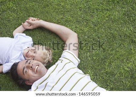 Portrait of cheerful father and young son lying on grass - stock photo