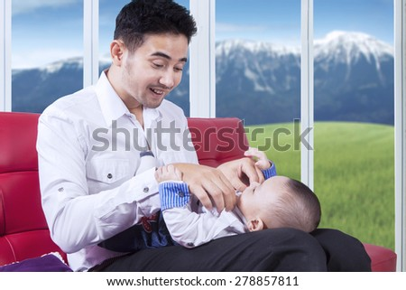 Portrait of cheerful father sitting on couch at home while replace his baby clothes - stock photo