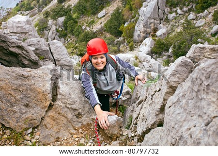 Portrait of cheerful female climber ascending a rock - stock photo