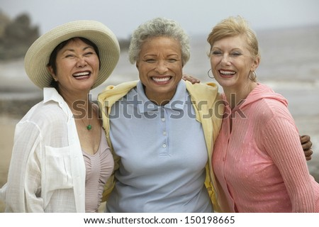 Portrait of cheerful female friends enjoying vacation at beach - stock photo