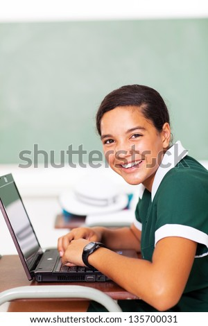 portrait of cheerful female middle school student using laptop in classroom - stock photo