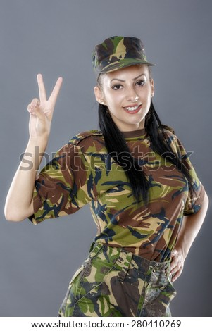 Portrait of cheerful female soldier gesturing peace sign - stock photo