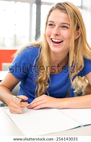 Portrait of cheerful female student writing notes in classroom - stock photo