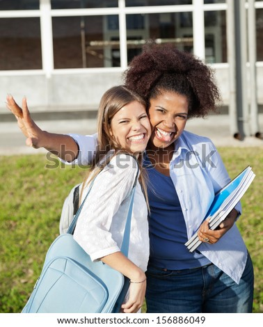 Portrait of cheerful female students making facial expressions on college campus - stock photo