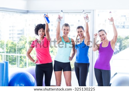 Portrait of cheerful fit women with water bottles standing in fitness studio