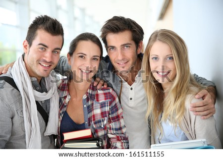 Portrait of cheerful friends at university - stock photo