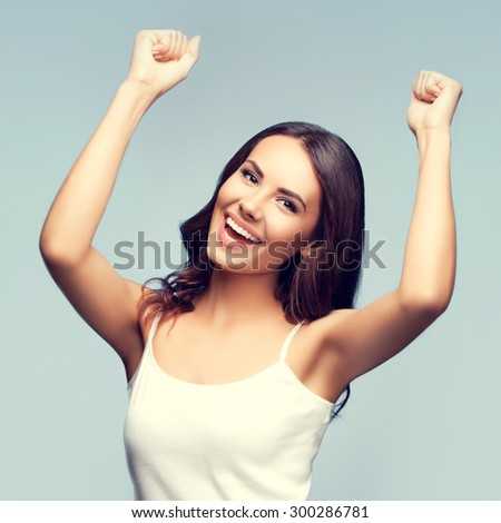 Portrait of cheerful gesturing smiling young woman in white tank top clothing - stock photo