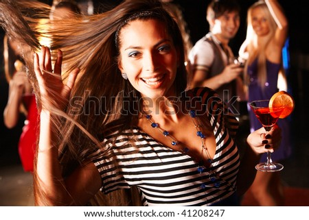 Portrait of cheerful girl dancing at party while smiling at camera - stock photo