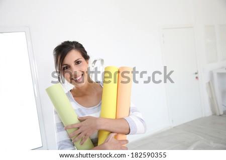 Portrait of cheerful girl holding wallpaper rolls - stock photo