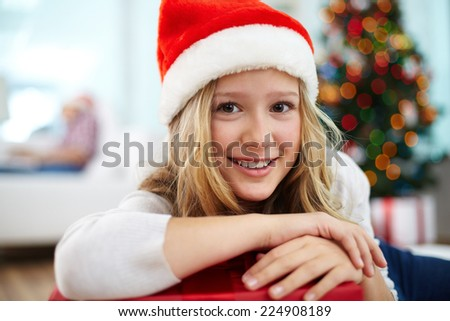 Portrait of cheerful girl in Santa cap looking at camera - stock photo