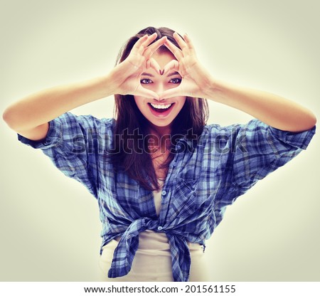Portrait of cheerful girl  looking through heart shape she made with her hands.  - stock photo