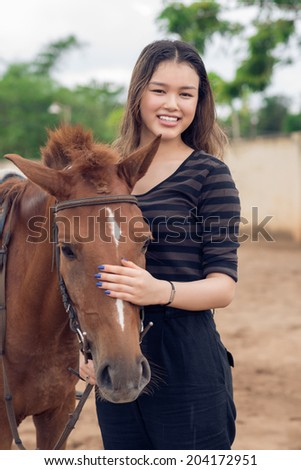 Portrait of cheerful girl stroking brown pony - stock photo